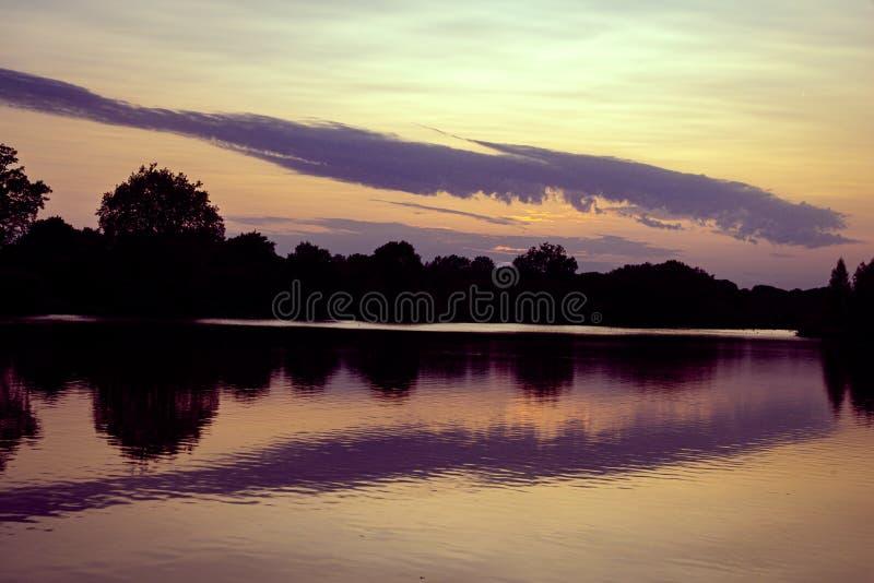 Coucher du soleil, région boisée et réflexions d'été dans le lac images stock