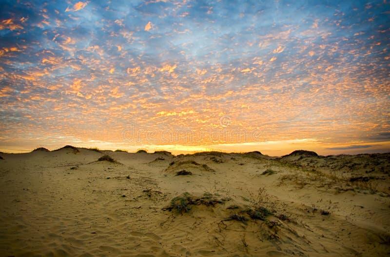 Coucher du soleil rare au-dessus des dunes de sable Nuages détaillés illuminés par le bas soleil image libre de droits