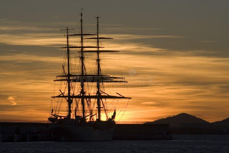Coucher du soleil romantique avec le sillouette de bateau   photos stock