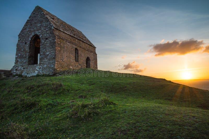 Coucher du soleil romantique sur la côte cornouaillaise avec lonelly la chapelle sur la falaise photographie stock libre de droits
