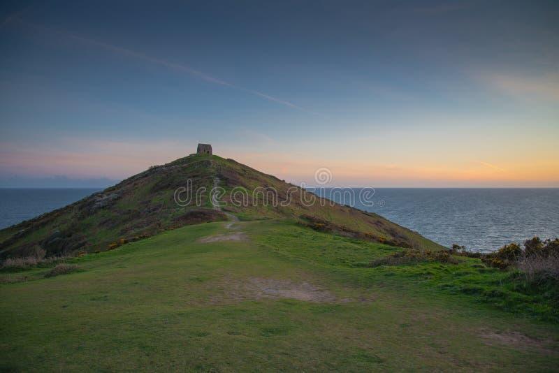 Coucher du soleil romantique sur la côte cornouaillaise avec lonelly la chapelle sur la falaise photographie stock