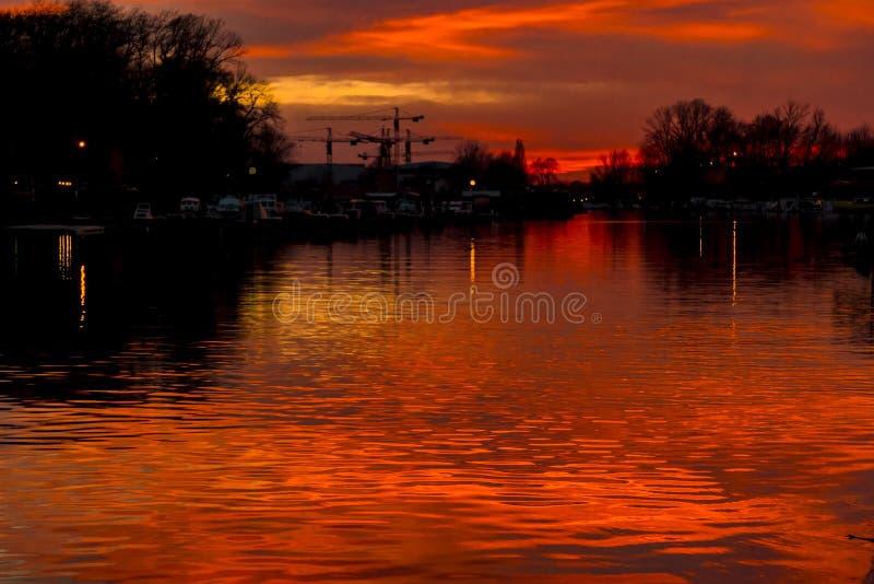 Coucher du soleil rouge au-dessus de rivière calme photo stock