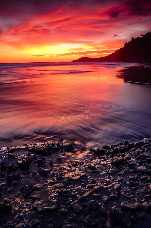 Coucher du soleil rouge derrière la roche photos stock