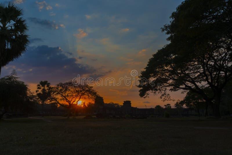 Coucher du soleil rouge lumineux dans Angkor Vat par les branches d'acacias photo libre de droits