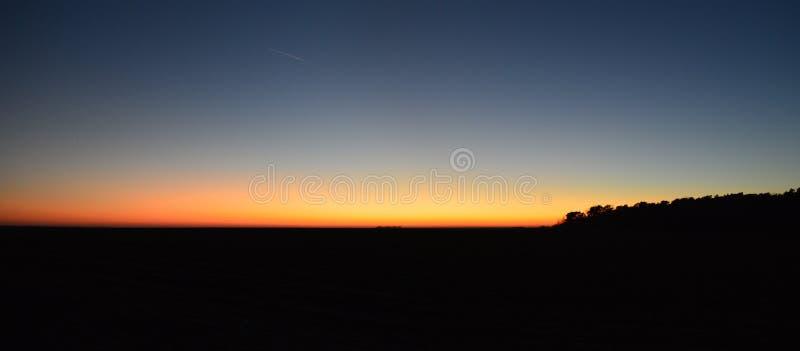Coucher du soleil sans nuages sur le champ plat photographie stock