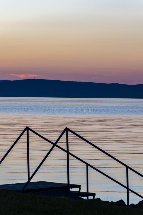 Coucher du soleil scénique au-dessus du lac calme, silhouette des escaliers menant pour arroser image stock