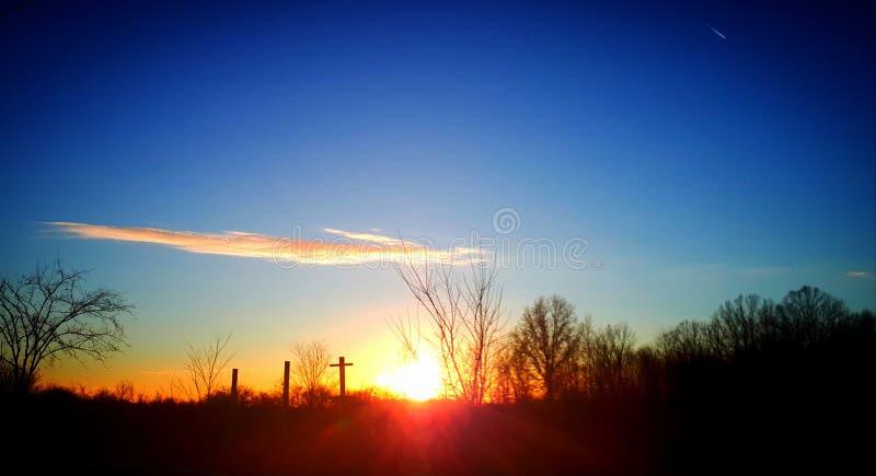 Coucher du soleil se reposant sur la croix image stock