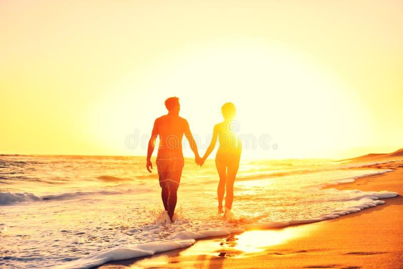 Coucher du soleil se tenant romantique de mains de couples de plage d'été photographie stock