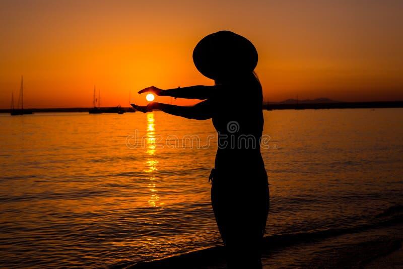 Coucher du soleil, silhouette sexy de femme Femme insouciante appr?ciant le coucher du soleil sur la plage Style de vie heureux M photo libre de droits