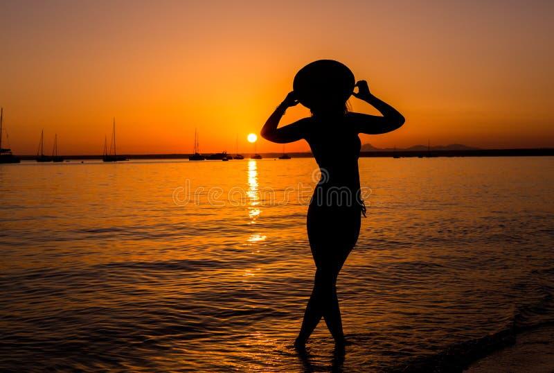 Coucher du soleil, silhouette sexy de femme Femme insouciante appr?ciant le coucher du soleil sur la plage Style de vie heureux M image libre de droits