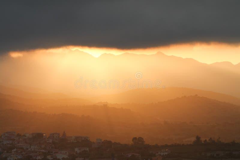 Coucher du soleil stupéfiant après la tempête Les rayons du soleil orange glissent sous un grand nuage noir illuminant les montag image libre de droits