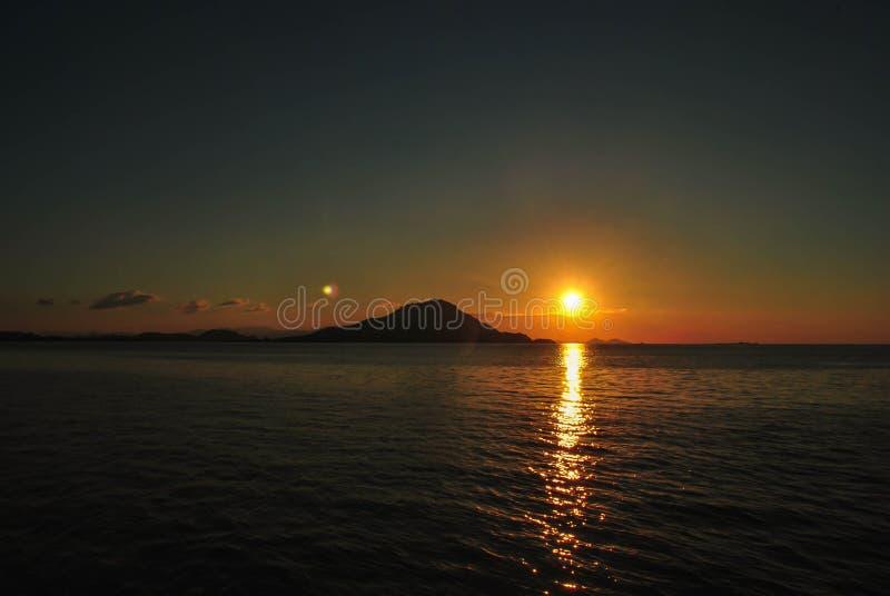 Coucher du soleil stupéfiant avec le fond orange de vagues de ciel et de mer Beau coucher du soleil en île tropicale de Komodo, L image libre de droits