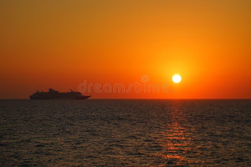 Coucher du soleil suggestif avec le bateau dans Santorini dans les îles de Cyclades photographie stock