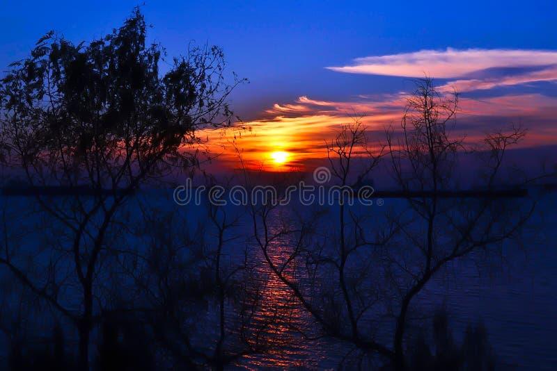 Coucher du soleil suggestif sur la mer dans un ciel bleu et orange image libre de droits