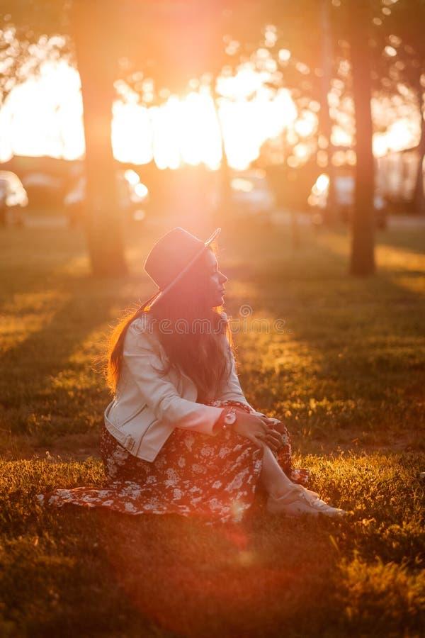 Coucher du soleil Sun Une fille dans un chapeau s'assied sur la pelouse images libres de droits