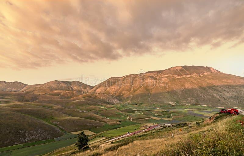 Coucher du soleil sur des montagnes et le paysage de champs Castelluccio di Norcia photos stock