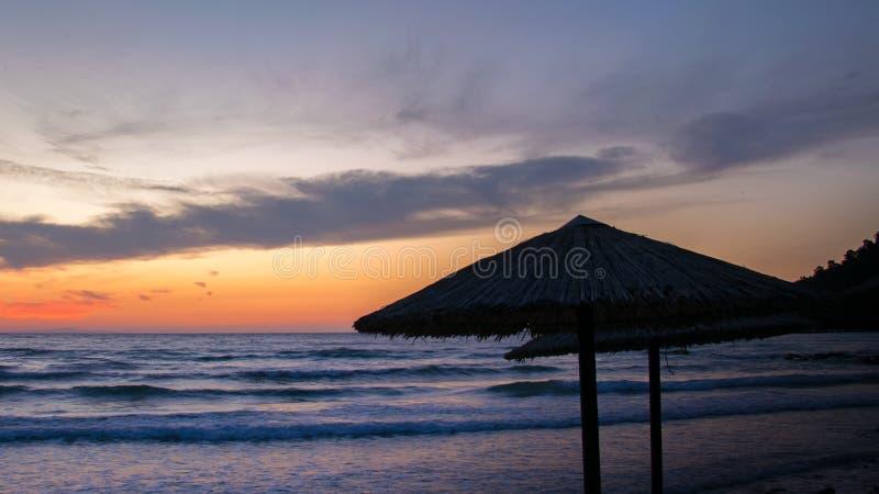 Coucher du soleil sur l'île grecque de Thassos avec un parapluie tubulaire avec les vagues bleues et le ciel orange images libres de droits