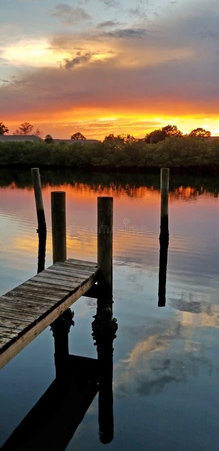 Coucher du soleil sur l'eau par un dock photo libre de droits