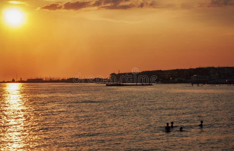 Coucher du soleil sur la mer avec des silhouettes des garçons jouant heureusement dans le Ca photo stock