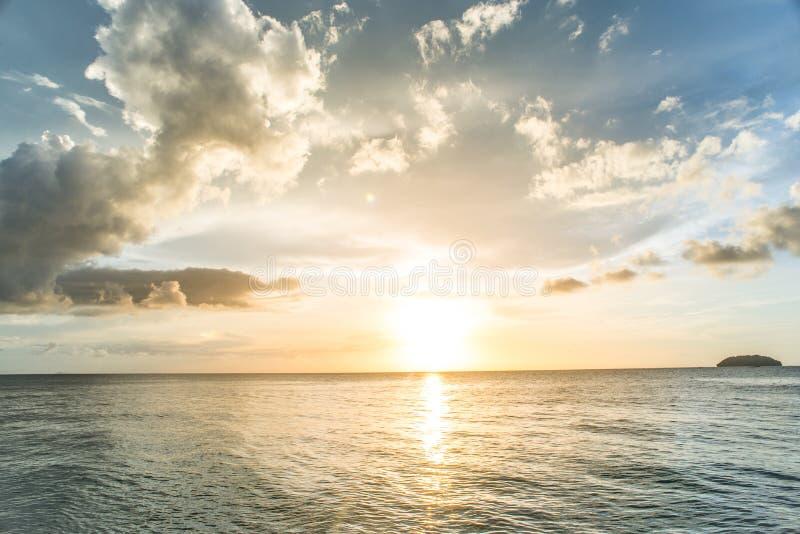 Coucher du soleil sur la mer avec le fond de ciel nuageux photos stock