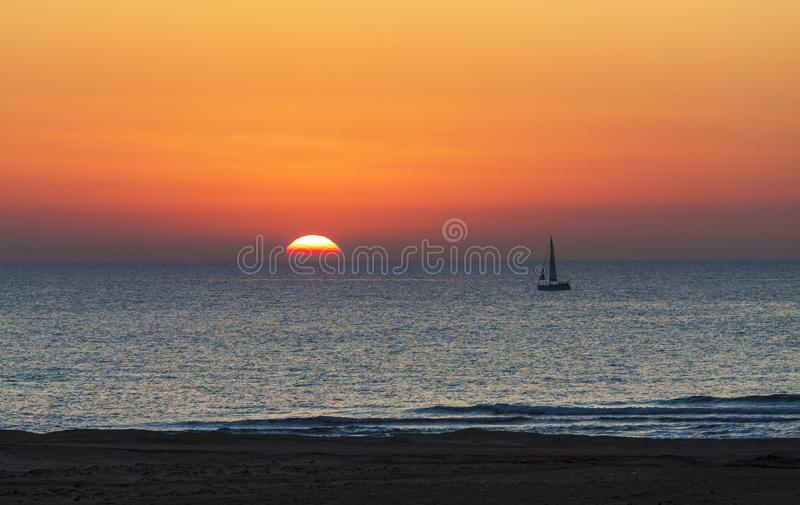 Coucher du soleil sur la mer avec la silhouette d'un yacht images stock