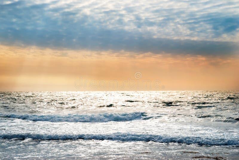 Coucher du soleil sur la mer bleue avec des vagues photo libre de droits