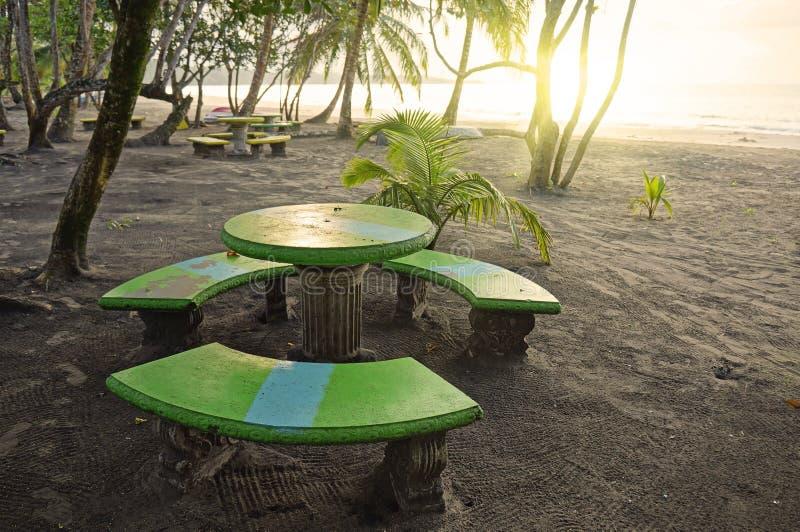 Coucher du soleil sur la plage avec la table ronde et les bancs photos libres de droits