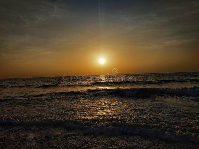 Coucher du soleil sur la plage avec le ciel dramatique image stock
