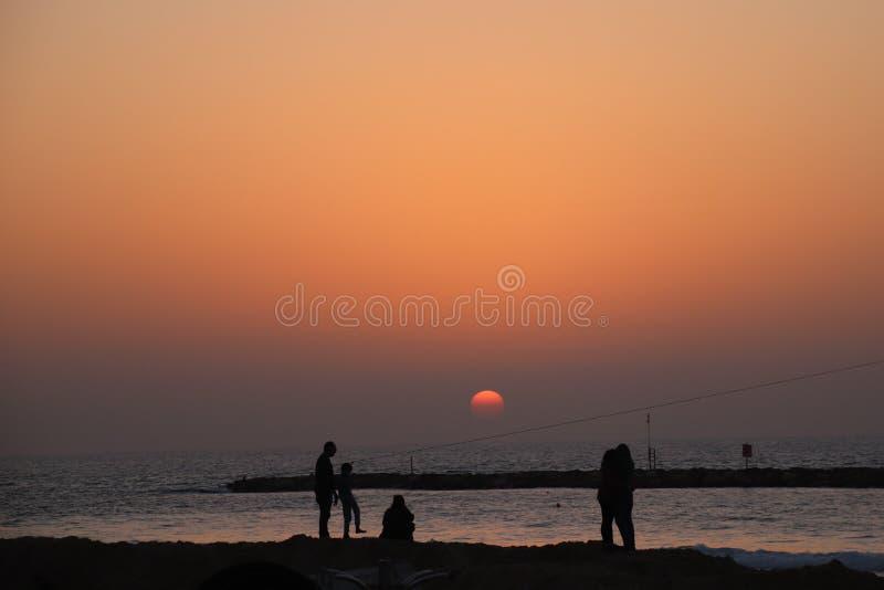 Coucher du soleil sur la plage avec le people& x27 ; silhouettes de s image libre de droits