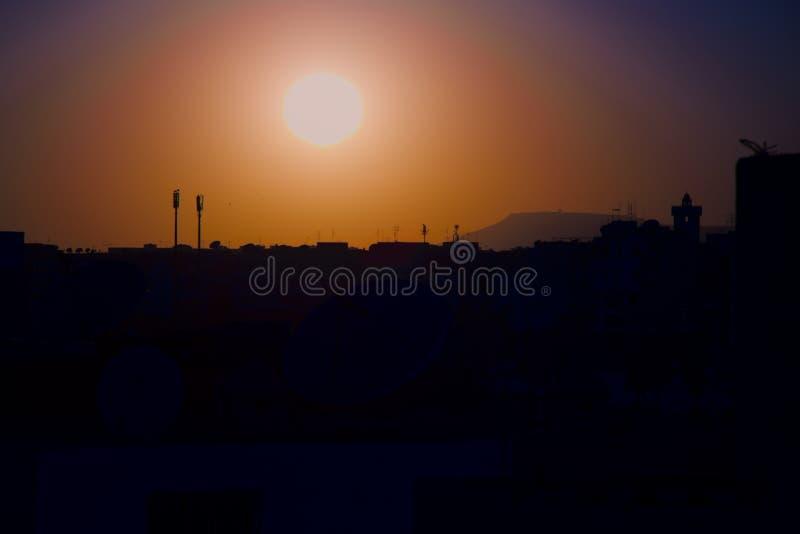 Coucher du soleil sur la ville d'Agadir Maroc avec les antennes et le minaret photo stock