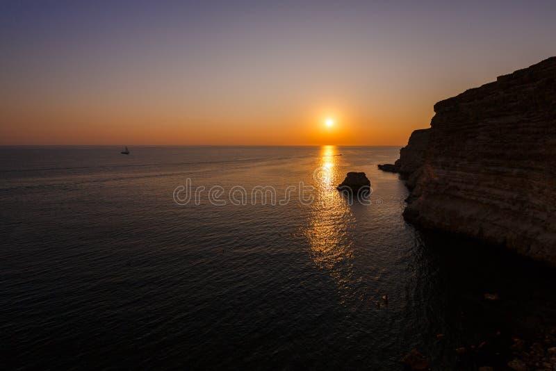 Coucher du soleil sur le bord de la mer rocheux images libres de droits