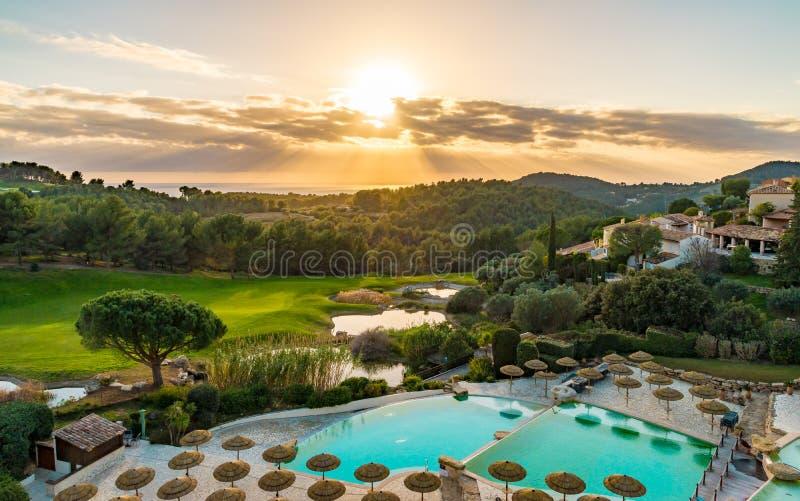 Coucher du soleil sur le terrain de golf et la piscine photo libre de droits