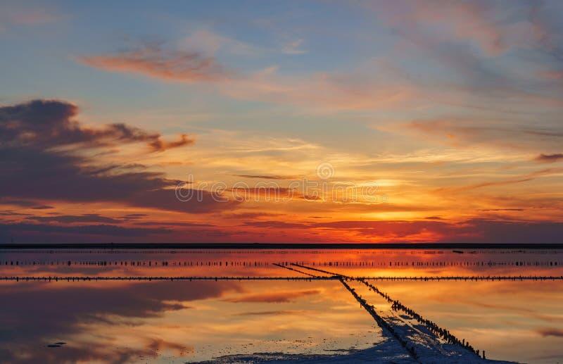 Coucher du soleil sur un lac de sel rose, une ancienne mine pour l'extraction du sel rose rang?e des chevilles en bois envahies a photos stock