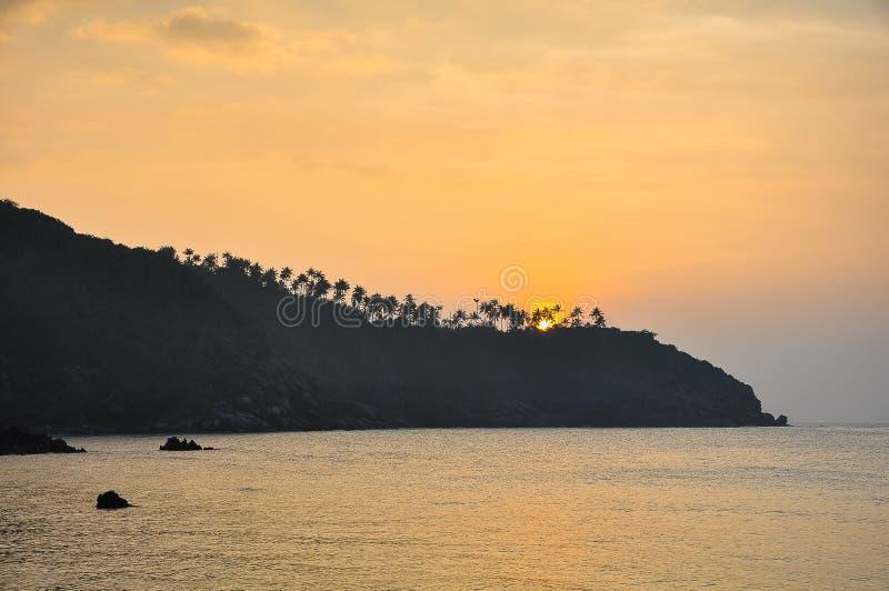 Coucher du soleil sur une île tropicale, silhouettes de palmiers sur les roches photo stock