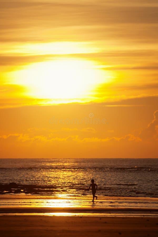 Coucher du soleil sur une plage avec la silhouette d'un gosse photos stock