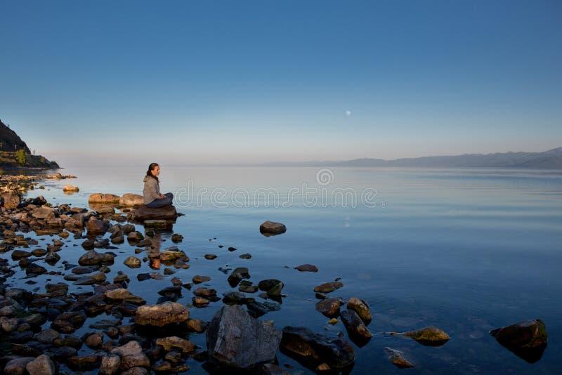Coucher du soleil tranquille au-dessus de la rivière La fille s'assied sur une grande pierre Soirée calme d'été, pleine lune photographie stock