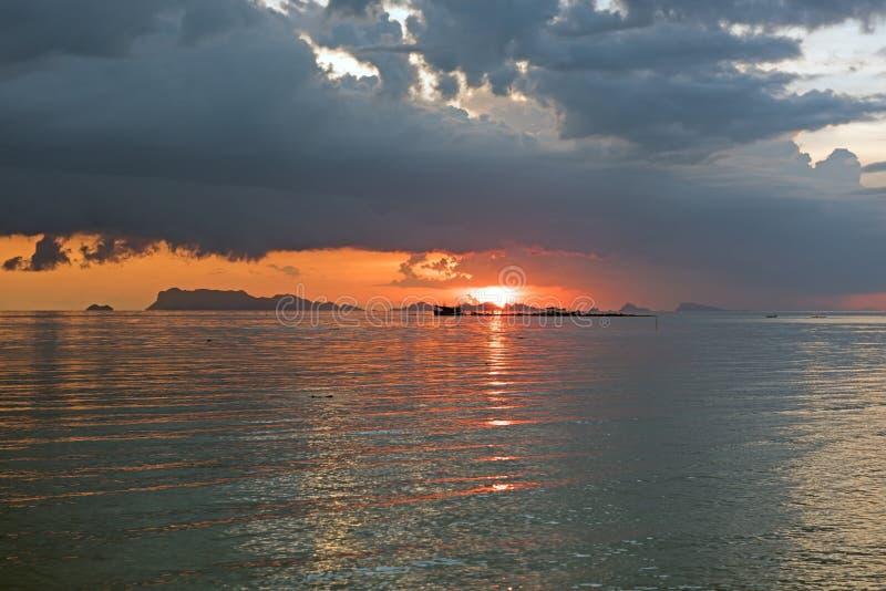 coucher du soleil tropical vibrant de paysage marin avec le fond foncé de nuage photo stock