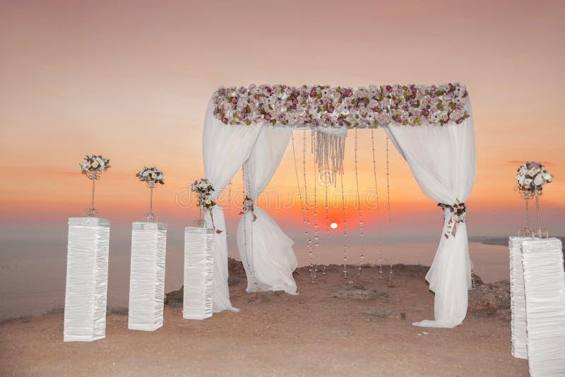 Coucher du soleil Voûte de cérémonie de mariage avec des arrangemen décoratifs de fleurs photo libre de droits