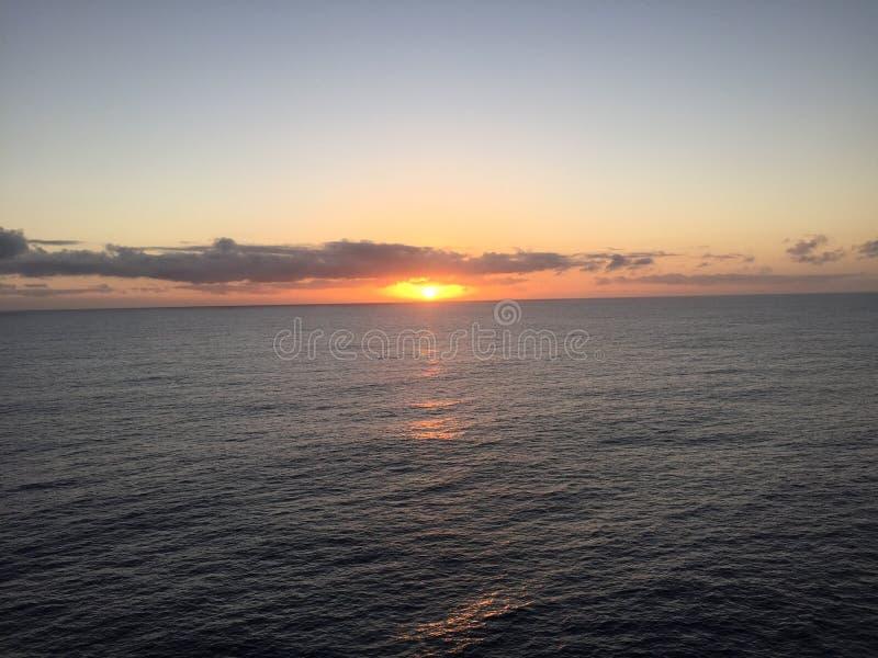 Couchers du soleil en mer image stock