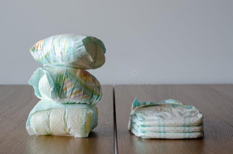 Couches-culottes nouvelles et utilisées de bébé sur le fond en bois de table images libres de droits