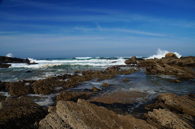 Couches inclinées bordées pointues de roche de lave exposées à marée basse photo libre de droits