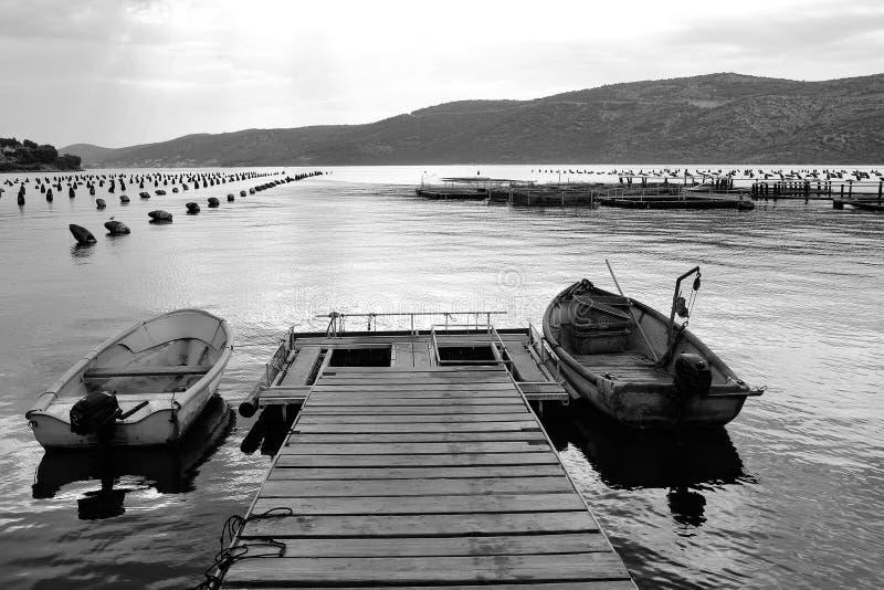 Couchette avec des bateaux Pilier en bois avec des bateaux de pêche image stock