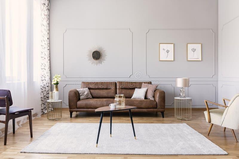 Couchtisch mit Vase und Becher mitten in elegantem Wohnzimmerinnenraum mit bequemem ledernem Sofa, stilvoller purpurroter Stuhl stockbilder