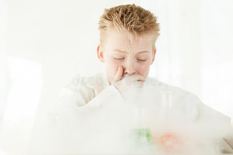 Coughing boy surrounded by dangerous chemicals. Coughing young boy wearing white lab coat and spiky blond hair surrounded by dangerous chemicals reacting and royalty free stock photo