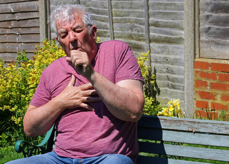 Coughing, colds, influenza or smokers cough.close up. A senior man outside and coughing. Bad chest and lungs through smoking. Cold or flue. closeup stock images