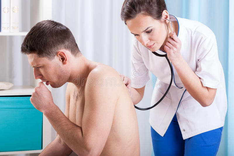 Coughing man having examination stock image