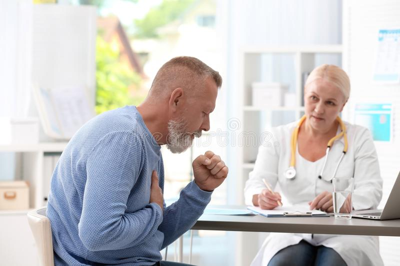 Coughing mature man visiting doctor royalty free stock images