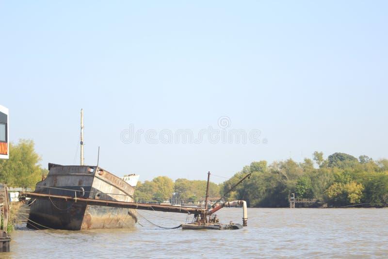 Couler le vieux bateau à la rivière du ` s de Lujan photographie stock libre de droits