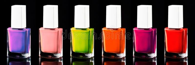 Couleurs au néon lumineuses de vernis à ongles du rouge à ultra-violet, d'isolement sur noir, bannière images stock