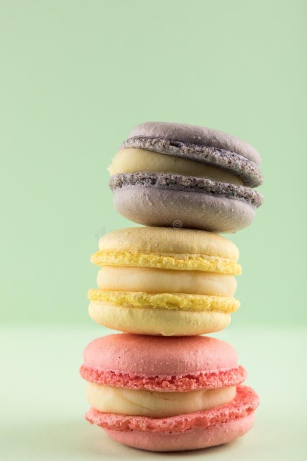 Couleurs de pastel de Macarons, pourpre, jaune et rose sur le fond vert photos libres de droits